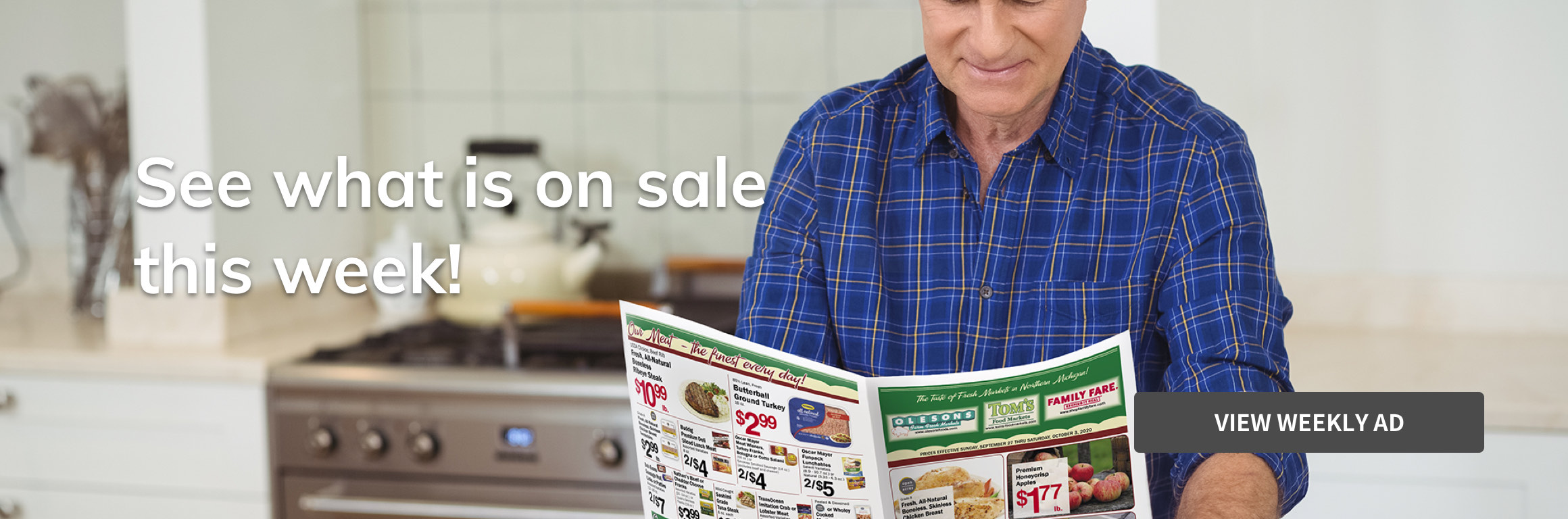 Man reading weekly ad in a kitchen.
